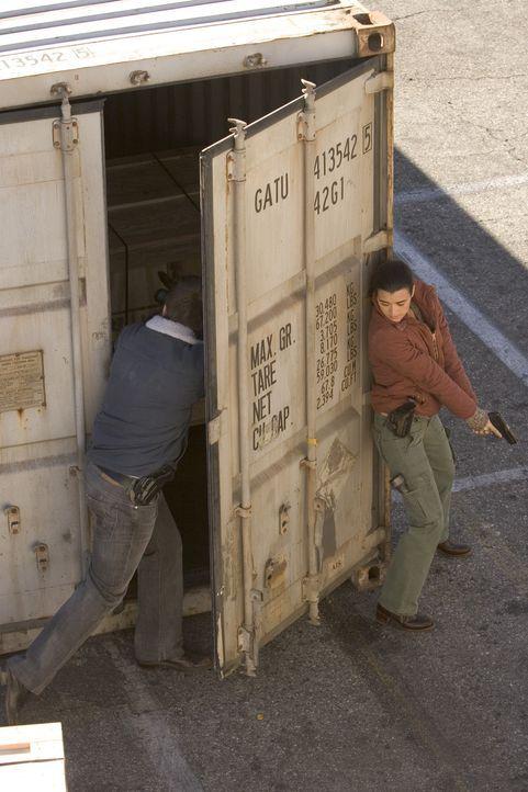 Ziva (Cote de Pablo, r.) und Tony (Michael Weatherly, l.) sind am Hafen von Norfolk. Sie laufen zwischen Containern umher, als plötzlich auf sie ge... - Bildquelle: TM &   2006 CBS Studios Inc. All Rights Reserved.