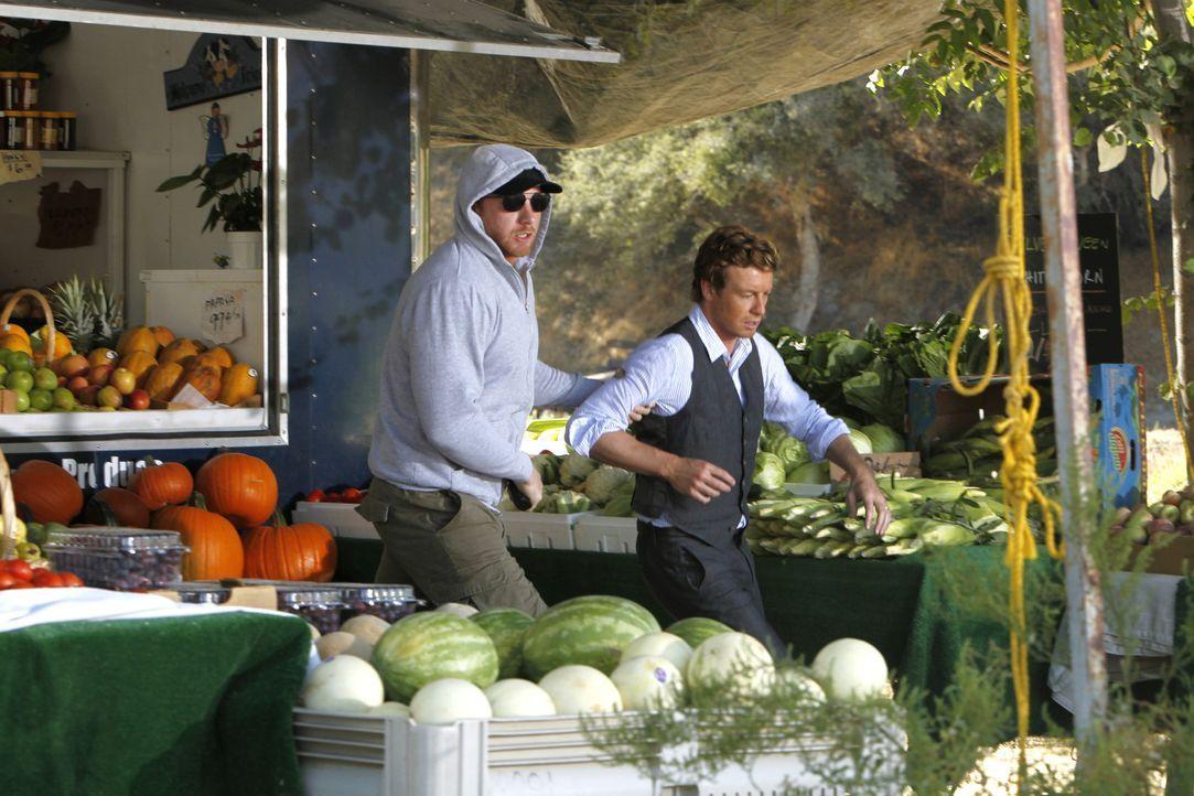 Patrick Jane (Simon Baker, r.) wird an einem Obststand vom Gangster Fred Kittel (Adam Dunnells, l.) entführt, nachdem dieser den Obsthändler ersch... - Bildquelle: Warner Bros. Television