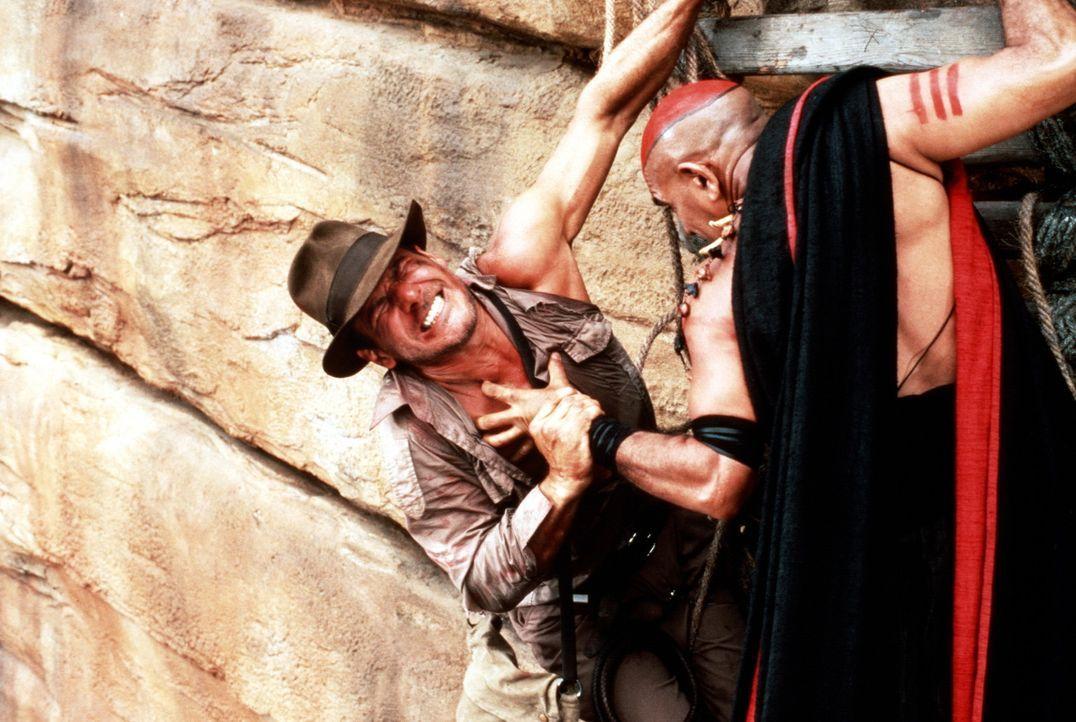 Mit Hilfe der schwarzen Magie der Todesgöttin Shiva droht der böse Hohepriester Mola Ram (Amrish Puri, r.), Indy (Harrison Ford, l.) das pochende... - Bildquelle: Paramount Pictures