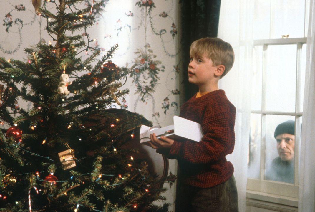 Während der nichtsahnende Kevin (Macaulay Culkin, l.) den Weihnachtsbaum schmückt, lauert Harry (Joe Pesci, r.) auf eine Gelegenheit, das Haus aus... - Bildquelle: 20th Century Fox Film Corporation