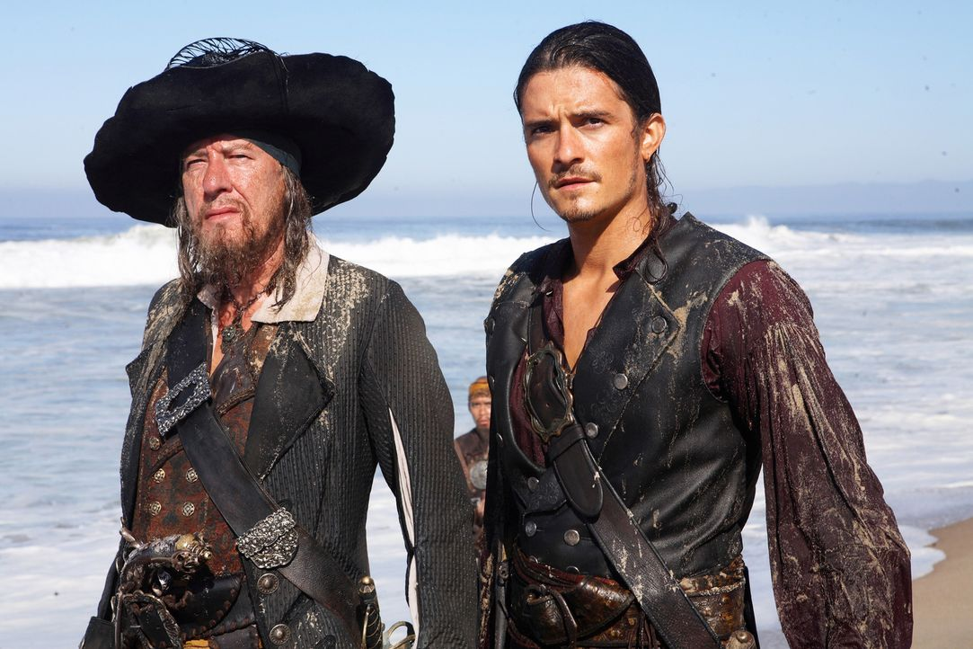 Turner (Orlando Bloom, r.), Swann und Barbossa (Geoffrey Rush, l.) wollen Jack Sparrow, der von einem Riesenkraken getötet worden ist, wiederbelebe... - Bildquelle: Disney Enterprises, Inc.  All rights reserved