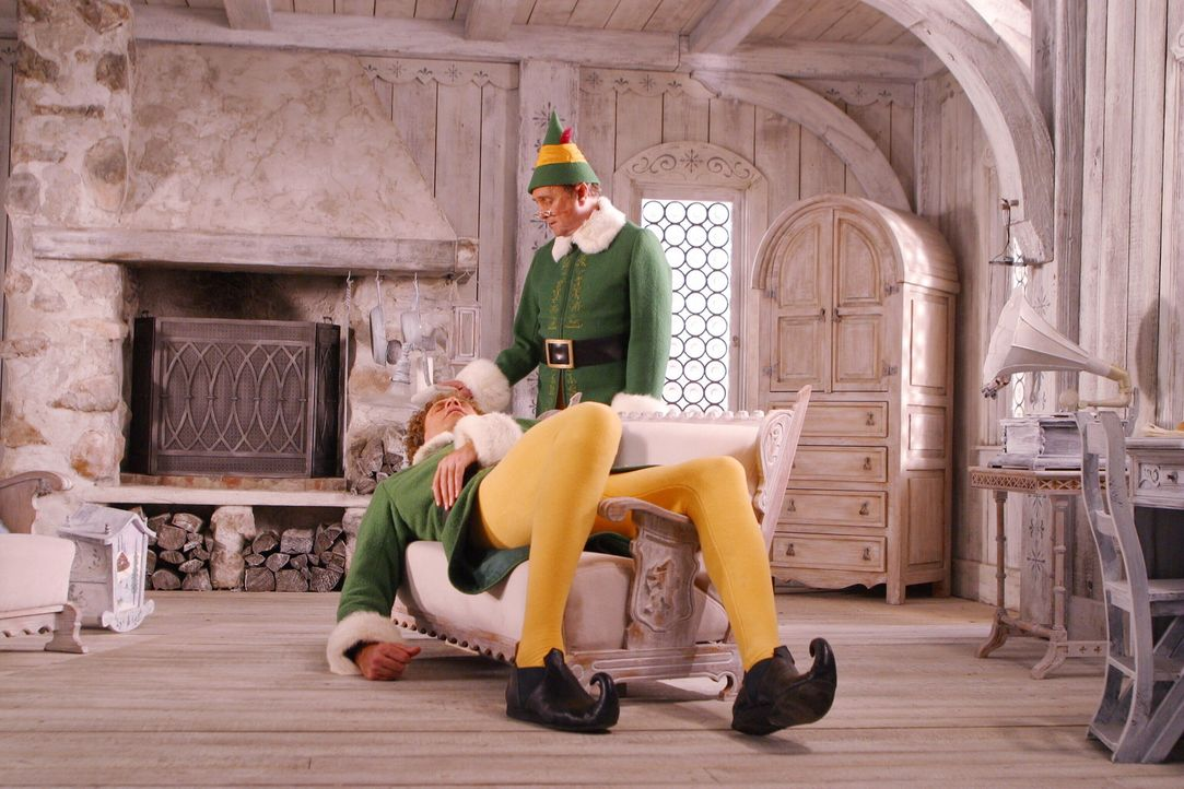 Papa Elf (Bob Newhart, r.) zieht Buddy (Will Ferrell, l.) auf. Eines Tages merkt der große Buddy, dass er nicht zu den Elfen passt und möchte desh... - Bildquelle: Warner Bros. Television