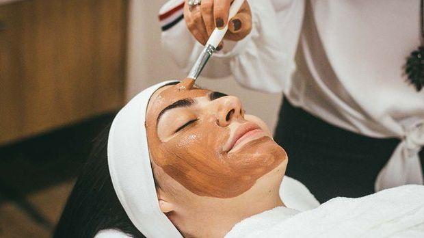 Frau mit braunen Haaren bekommt Heilerde-Maske aufgetragen