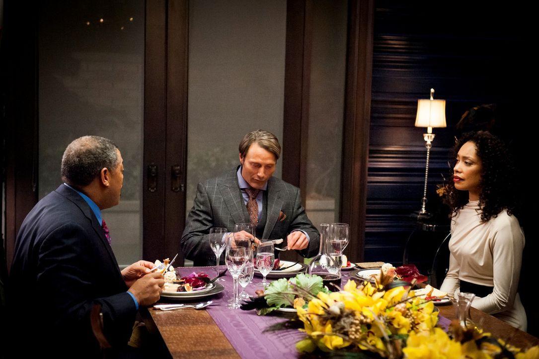 So gut es Jack (Laurence Fishburne, l.) und Bella (Gina Torres, r.) auch versuchen, ihre Missstimmung vor Dr. Hannibal Lecter (Mads Mikkelsen, M.) z... - Bildquelle: Brooke Palmer 2012 NBCUniversal Media, LLC