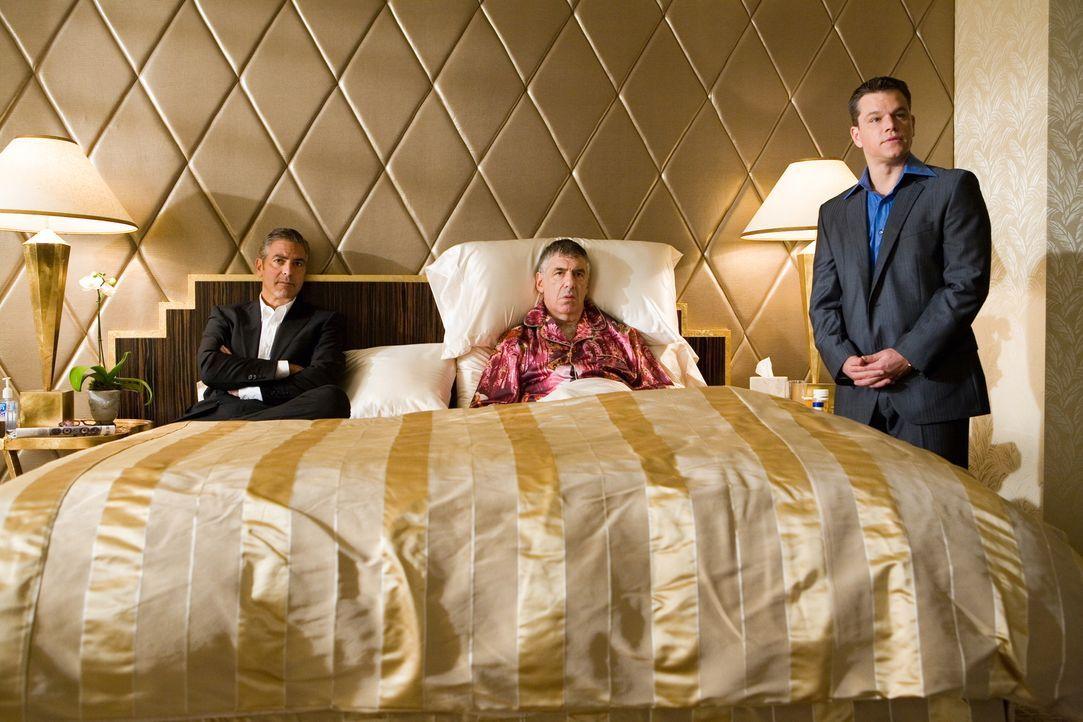 Reuben Tishkoff (Elliot Gould, M.), einer von Danny Oceans (George Clooney, l.) ursprünglichen Elf, wird von Kasinobesitzer Banks übel über den Tisc... - Bildquelle: TM &   Warner Bros. All Rights Reserved