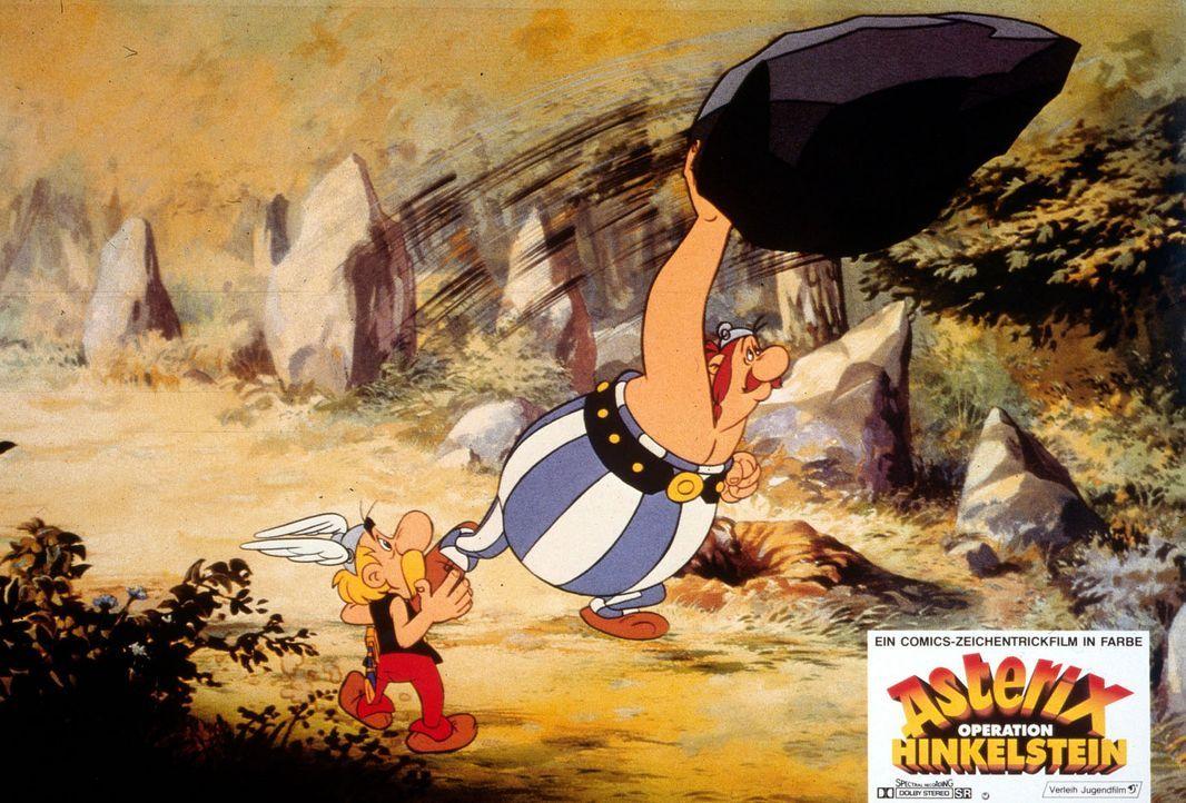 Asterix (l.) ahnt es schon. Obelix' (r.) Hinkelsteinwurf geht voll daneben. Statt eine römische Patrouille zu erledigen, begräbt der Stein den Druid... - Bildquelle: Jugendfilm-Verleih GmbH