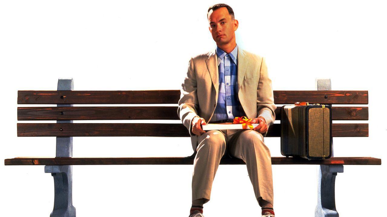 Neben sich ein gepackter Koffer und auf seinen Knien eine Packung Pralinen. So sitzt Forrest Gump (Tom Hanks) geduldig an einer Bushaltestelle - Bildquelle: Paramount Pictures