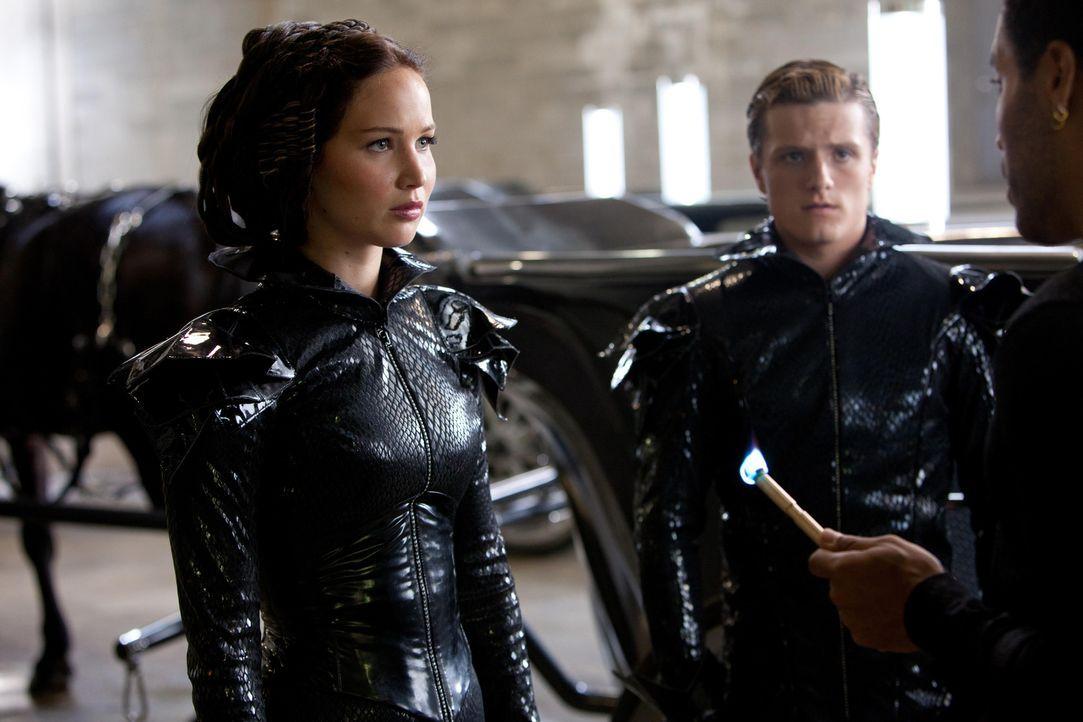 Dank des ausgefallenen Stylings von Cinna (Lenny Kravitz, r.) gelingt es Katniss (Jennifer Lawrence, l.) und Peeta (Josh Hutcherson, M.), schon in d... - Bildquelle: Studiocanal GmbH