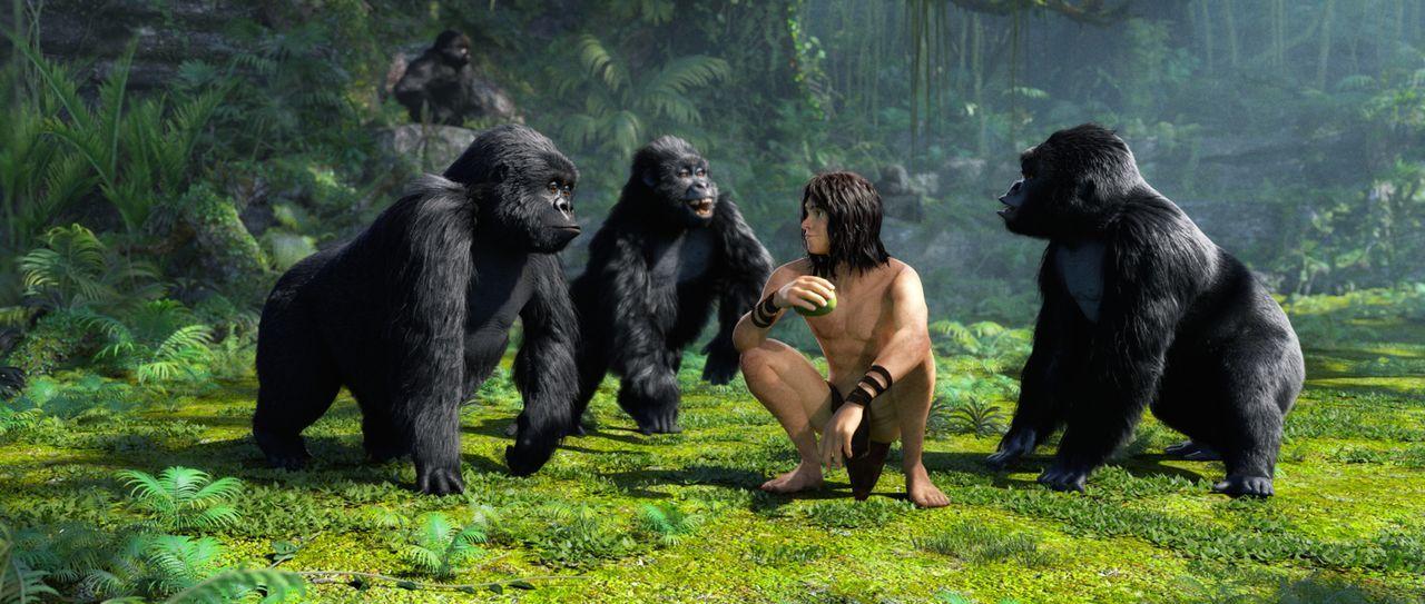 Wie einer von ihnen sitzt Tarzan inmitten der Affenbande im Grass des Dschungels. - Bildquelle: Constantin Film