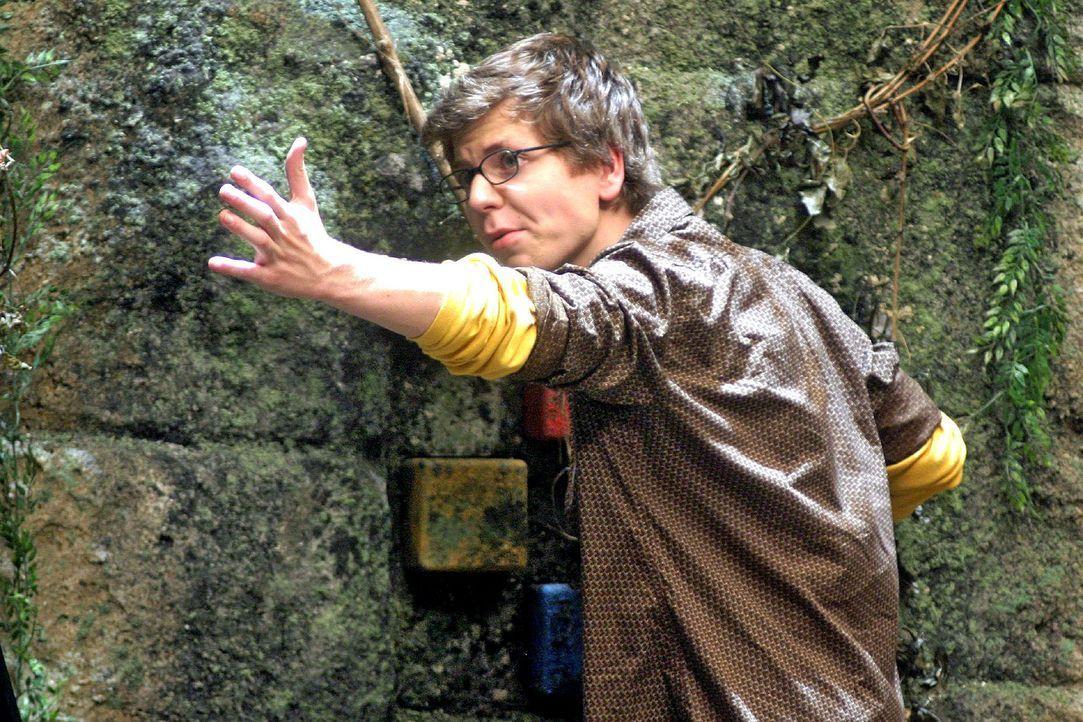Ron (Stefan Miess) wendet sich von dem Abgrund ab und betrachtet die Felswand hinter sich genauer. Er findet vier handtellergroße, viereckige Stein... - Bildquelle: Sat.1