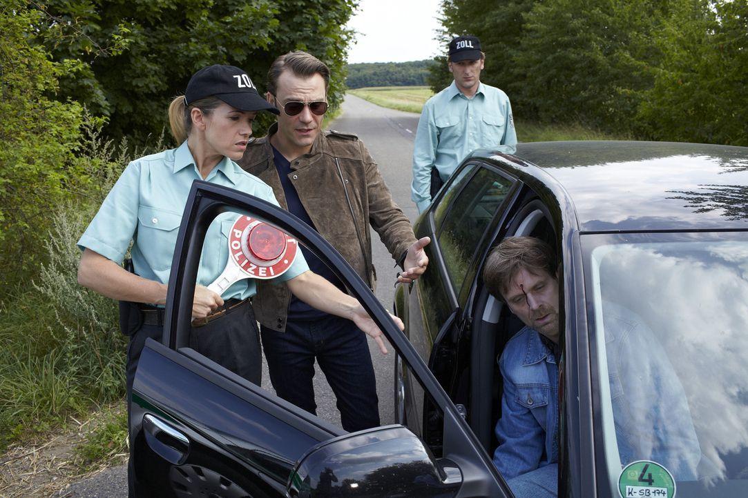 Die beiden Zollbeamten Carla (Anke Engelke, l.) und Nick (Kai Lentrodt, hinten) halten einen verdächtigen Wagen auf einer Landstraße an, um ihn nach... - Bildquelle: Guido Engels SAT.1