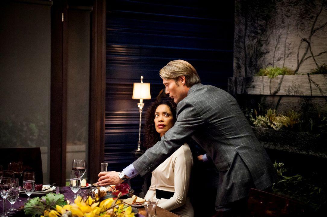 Vom feinen Geruchssinn Dr. Hannibal Lecters (Mads Mikkelsen, r.) ist Bella Crawford (Gina Torres, l.) schwer beeindruckt. - Bildquelle: Brooke Palmer 2012 NBCUniversal Media, LLC