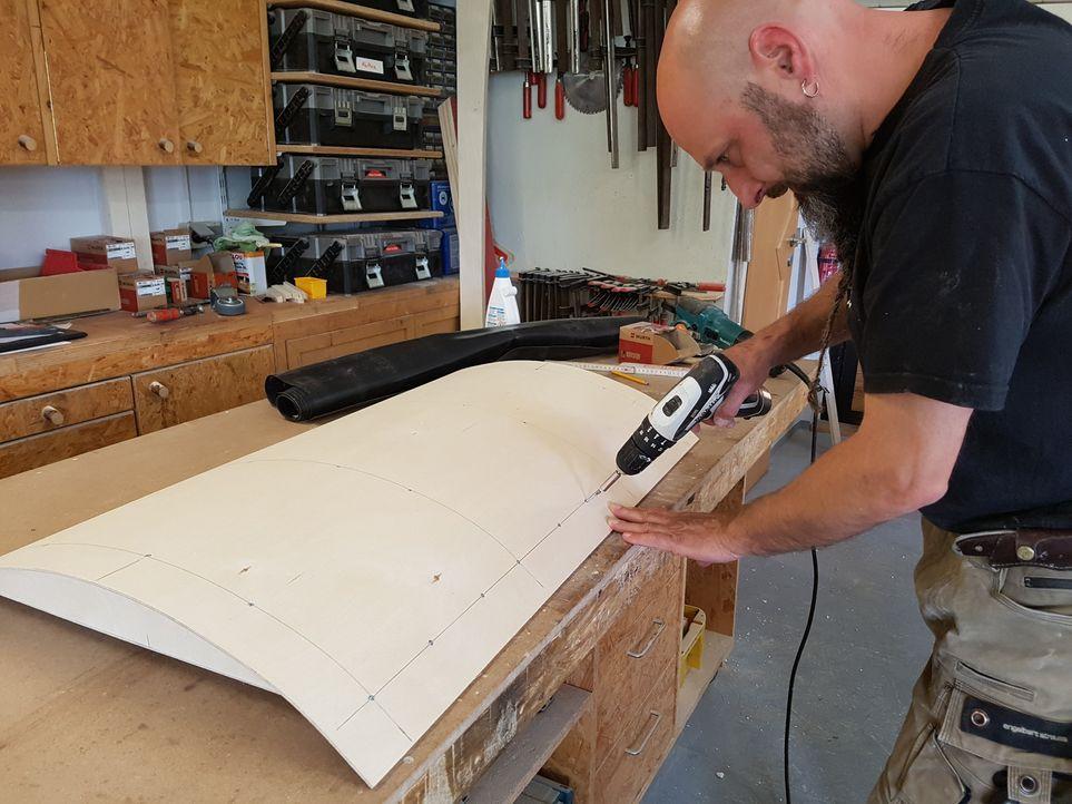 12. Schritt: Eine dünne Sperrholzplatte wird über die Dachträger gelegt und ...
