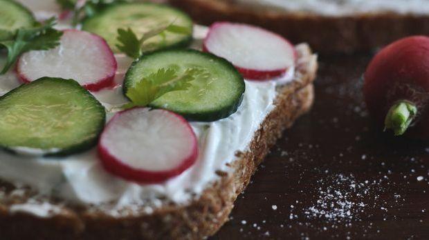 Vollkornbrot mit Frischkäse, Gurken und Radieschen belegt, versorgt Ihren Kör...