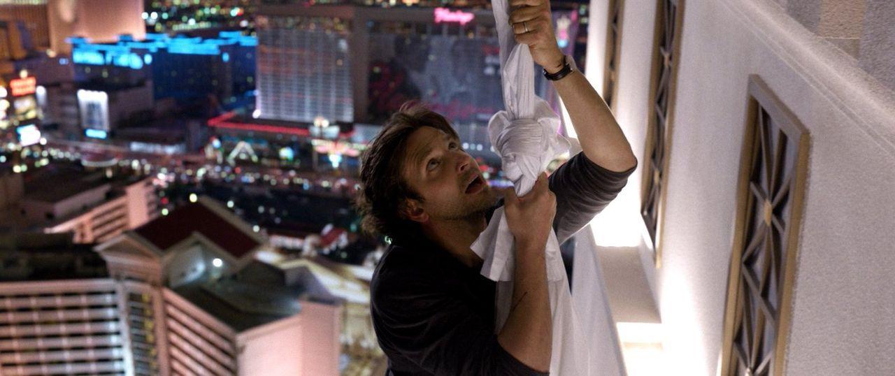 Jetzt hilft nur noch beten! Phil (Bradley Cooper) versucht sich mit Hilfe von Handtüchern abzuseilen, während Alan ihn absichern soll. Kann das gutg... - Bildquelle: 2013 Warner Brothers
