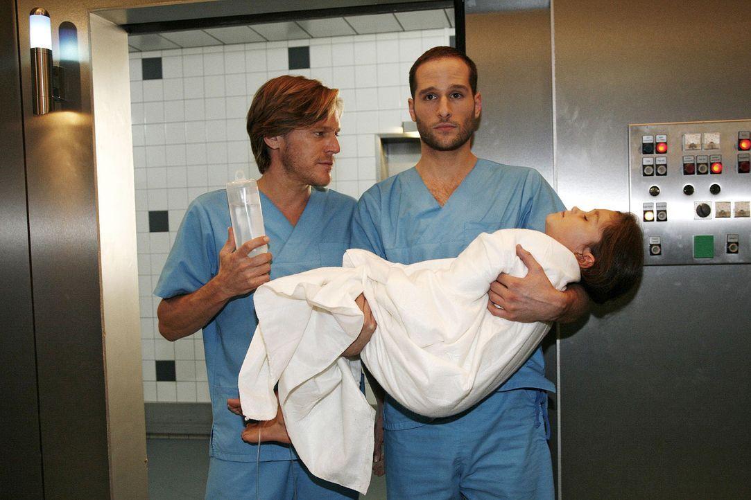 Christian (Tobias Kay, l.) und Jens (Lee Rychter, r.) lassen sich in letzter Minute auf die risikoreiche Operation der kleinen Nina (India Fahey, li... - Bildquelle: Mosch Sat.1