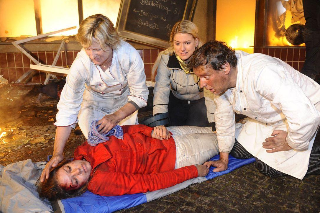 Katja (Karolina Lodyga, liegend) ist schwer verletzt aus den Flammen geborgen worden. Susanne (Heike Jonca, l.), Anna (Jeanette Biedermann, M.) und... - Bildquelle: SAT.1