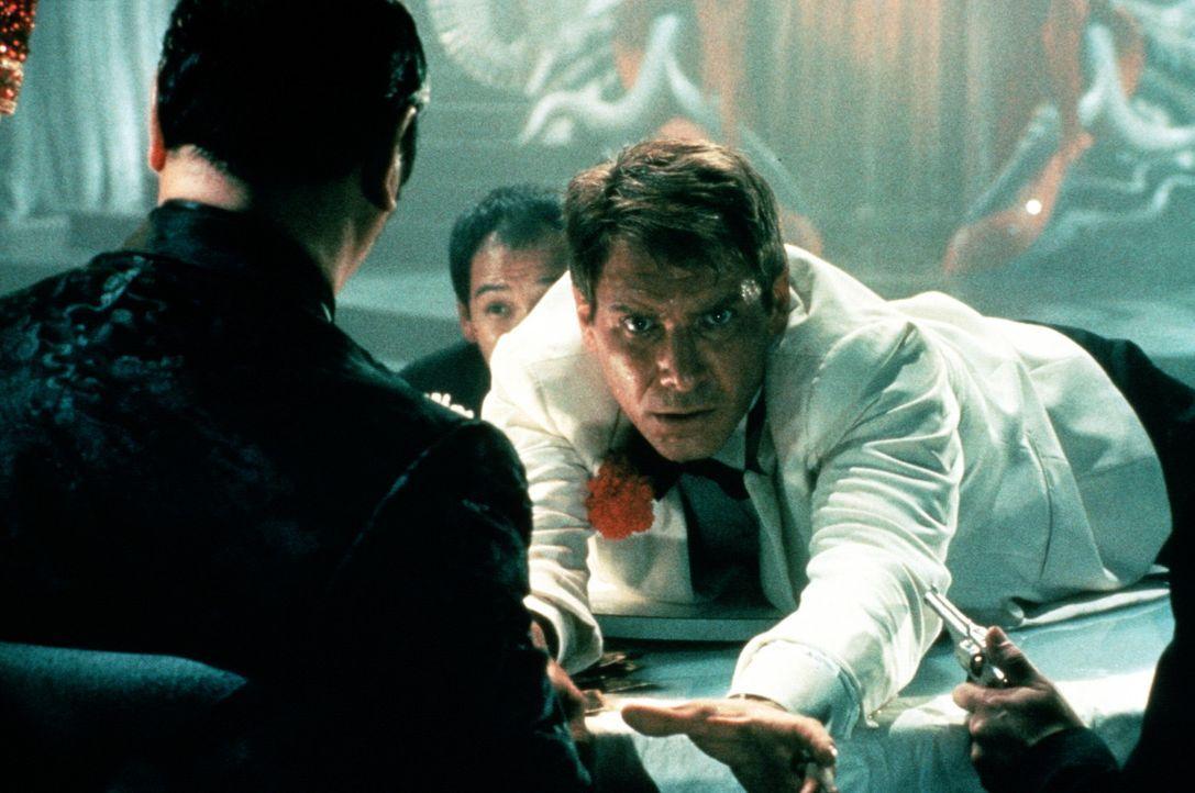 Hinterlistig versucht der Gangsterkönig Lao Che (Roy Chiao, l.), Dr. Jones (Harrison Ford, M.) bei dem Deal zu betrügen, und tut Gift in dessen Ch... - Bildquelle: Paramount Pictures