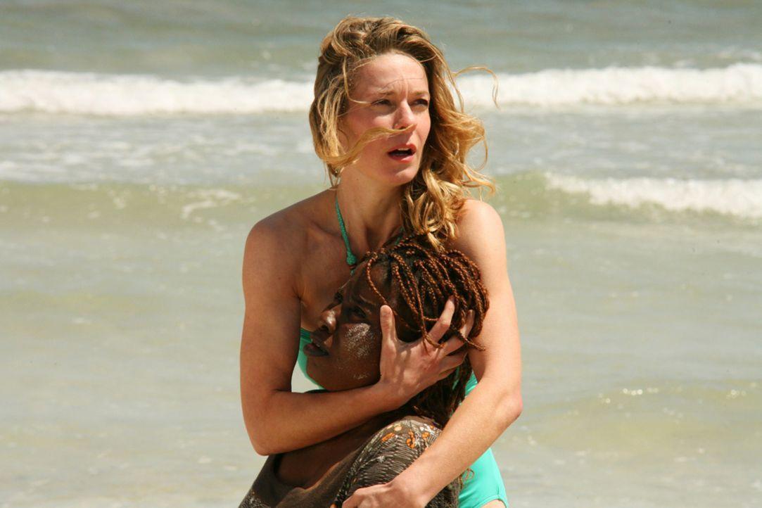 Während Mona (Lisa Martinek) einer der Flüchtlingsfrauen, die völlig entkräftet am Strand ankommen, hilft, stürzen Polizisten der Guardia Civil... - Bildquelle: Volker Roloff SAT.1