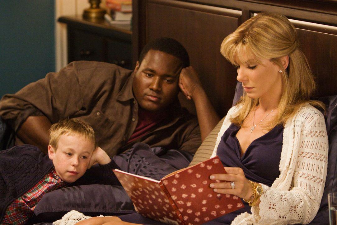 Als der obdachloser Teenager Michael Oher (Quinton Aaron, l.) zufällig auf Leigh Anne Tuohy (sandra Bullock, r.) und ihre Familie (Jae Head, M.) tr... - Bildquelle: Warner Brothers