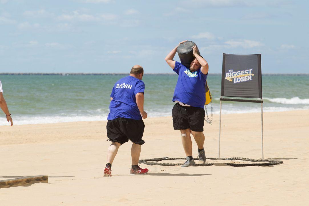 Es geht um ein Bonus-Kilo und Lukas (r.) und Björn (l.) geben alles, um den schweren Sandsack durch den tiefen Sand ans weit entfernt liegende Ziel... - Bildquelle: Enrique Cano SAT.1