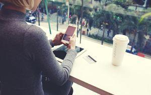 Junge Dame mit Kaffee beim Onlinebanking mit Smartphone und Tablet