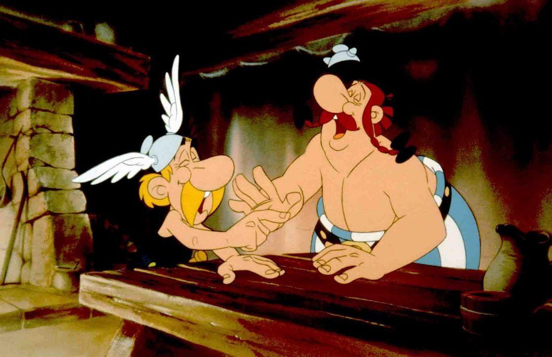 Asterix (l.) und Obelix (r.) lachen sich krank über die plumpen Tricks des betrügerischen Sehers ... - Bildquelle: Jugendfilm-Verleih GmbH