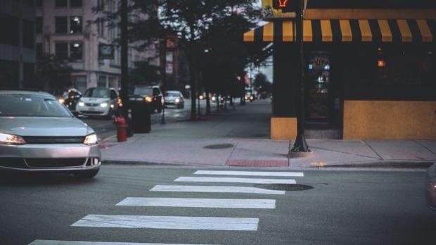 Autos in der Kurve eines Kreisverkehrs, dunkle Lichtstimmung