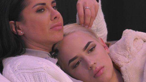 Gina hat ihren Kopf auf Marias Brust gelegt. Maria trägt eine weiße Strickjac...