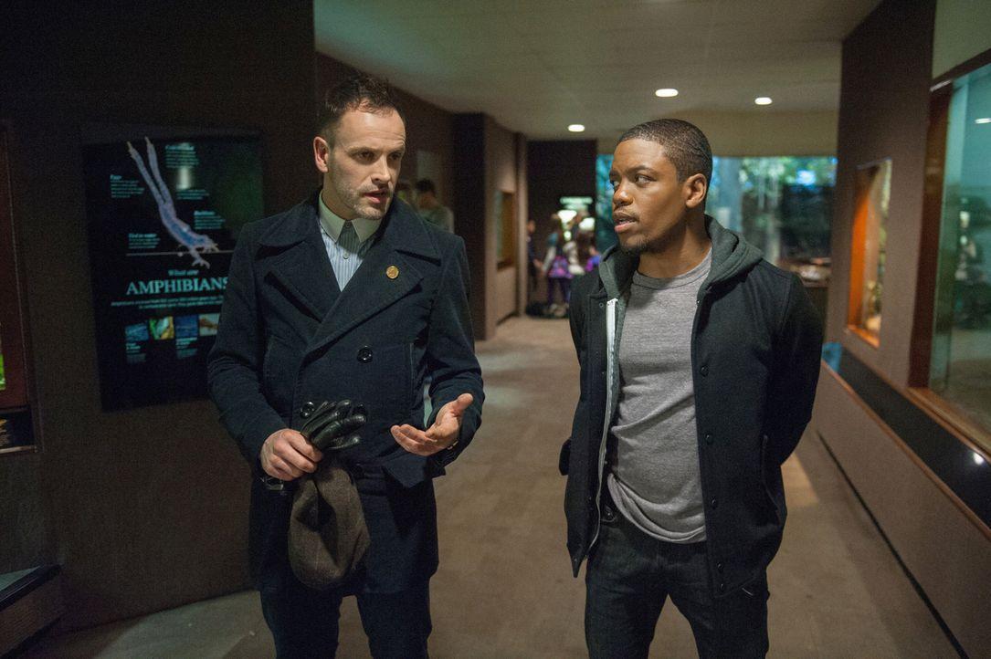 Während Watson anderweitig beschäftigt ist, muss Holmes (Jonny Lee Miller, l.) mit Bell (Jon Michael Hill, r.) zusammen arbeiten ... - Bildquelle: CBS Television